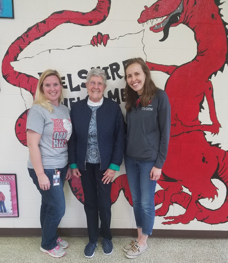 Delshire Snack Sack team members in front of the school dragon mural