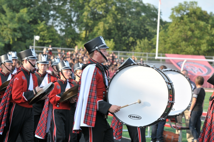 Drumline marching at football game.